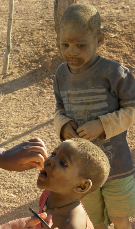 A dust-covered child receives a Viramin A oral booster, Kunene Namibia National Immunisation Days 2011 Round One