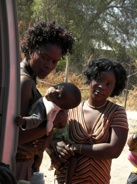 Two mothers with their children watch immunisations and wait their turn, Kunene Namibia National Immunisation Days 2011 Round One